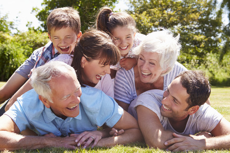 Multi Generation Family Piled Up In Garden Together Standard-Bild