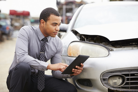 seguros: Ajustador de pérdida Usando Tableta digital En Wreck Inspección de coches Foto de archivo