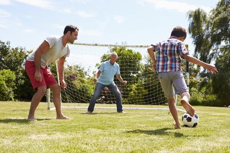 Abuelo, Nieto y el padre que juega a fútbol en el jardín