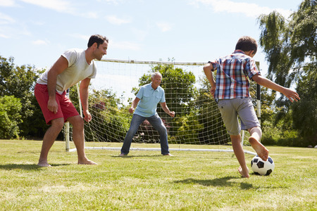 personen: Grootvader, kleinzoon en vader voetballen in de tuin