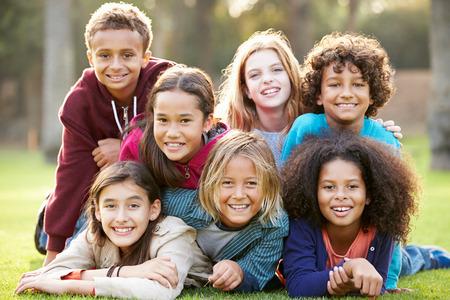 bambini: Gruppo di bambini che si trovano sull'erba insieme nel parco Archivio Fotografico