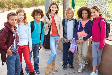 niño con mochila: Grupo de niños jovenes que cuelgan hacia fuera en patio Foto de archivo