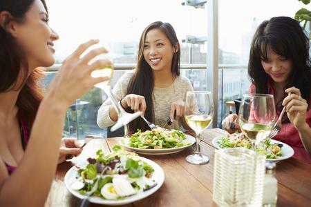 Drei weibliche Freunde genießen Mittagessen im Rooftop Restaurant