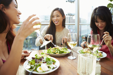 Three Female Friends Enjoying Lunch At Rooftop Restaurant Stock Photo