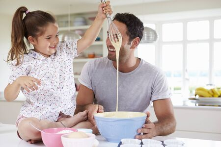 messy kitchen: Father And Daughter Baking Cake In Kitchen