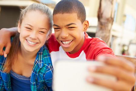 pareja de adolescentes: Pareja adolescente que se sienta en el banco en el centro comercial Tomando selfie