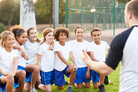 niños jugando: Formación del equipo de fútbol Juventud Con Entrenador Foto de archivo