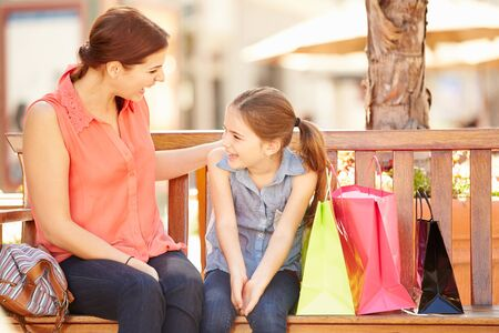 shopper: Mother And Daughter Sitting On Seat In Mall Together Stock Photo