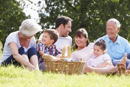 familia pic nic: Multi generacional disfrutan de comida campestre En Campo