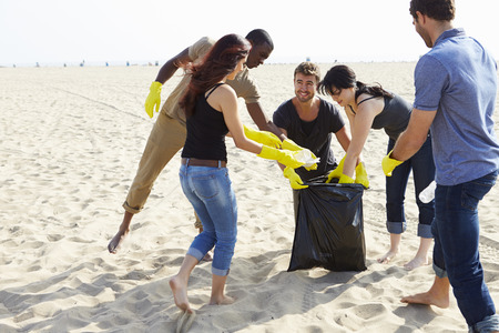 beach: Group Of Volunteers Tidying Up Rubbish On Beach