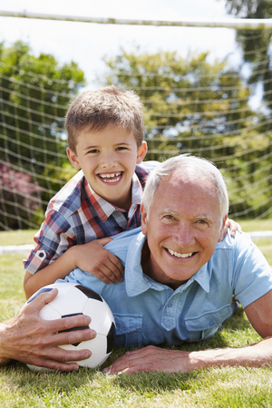 grandson: Portrait Of Grandfather And Grandson With Football Stock Photo