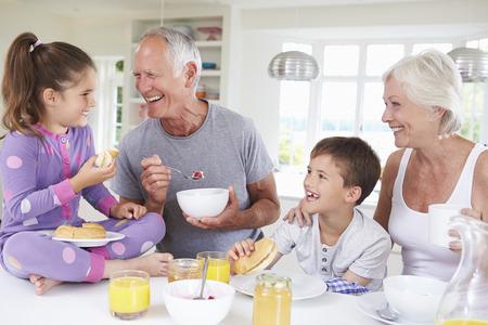 niños desayunando: Abuelos con los nietos Comer el desayuno en cocina Foto de archivo
