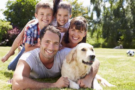 familia abrazo: Familia que se relaja en jardín con perro de mascota Foto de archivo
