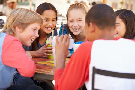 hablando por celular: Grupo de niños en la CAF Mirando a texto en el teléfono móvil Foto de archivo