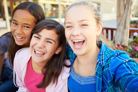 mixed race girl: Group Of Girls Hanging Out In Mall Together Stock Photo
