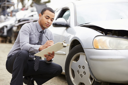 Loss Adjuster Inspecting Car Involved In Accident Banque d'images