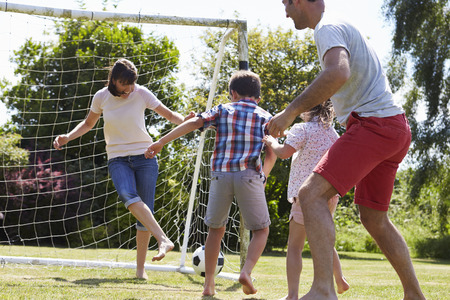 8 years: Family Playing Football In Garden Together