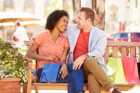 mixed races: Young Couple Resting With Shopping Bags Sitting In Mall