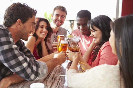barra: Grupo de amigos que disfrutan de la bebida Al aire libre en la azotea Bar Foto de archivo