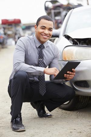 black car: Loss Adjuster Using Digital Tablet In Car Wreck Inspection Stock Photo