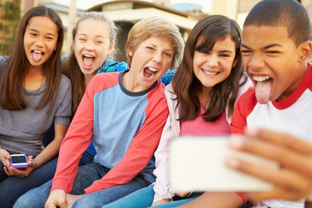 five years old: Group Of Children Sitting On Bench In Mall Taking Selfie Stock Photo