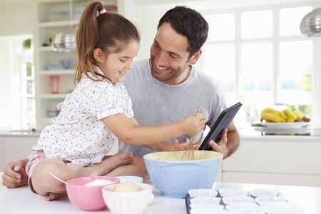 padre e hija: Padre e hija Siguiendo la receta de la torta en la tableta digital Foto de archivo