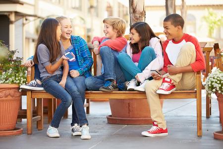 niños sentados: Grupo de niños sentados en el banquillo en el centro comercial Foto de archivo