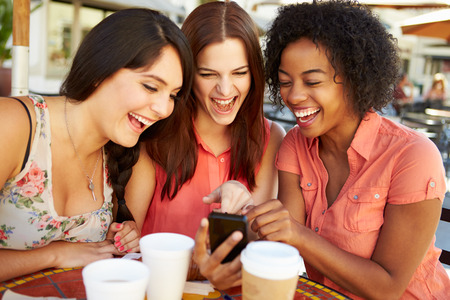 caf: Three Female Friends Reading Text Message In Caf�