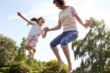 Moeder en dochter Bouncing op Trampoline Together Stockfoto