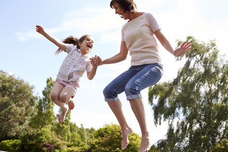 two parents: Mother And Daughter Bouncing On Trampoline Together