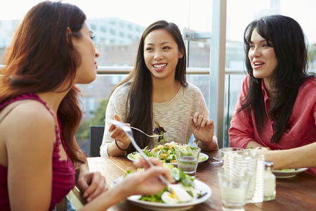 Three Female Friends Enjoying Lunch At Rooftop Restaurant Standard-Bild