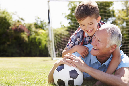 having fun: Portrait Of Grandfather And Grandson With Football Stock Photo