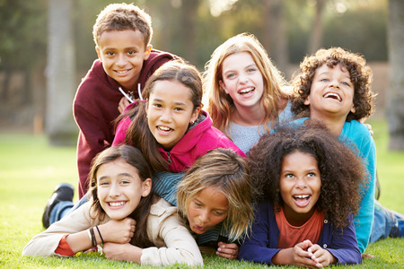 outdoor: Group Of Children Lying On Grass Together In Park Stock Photo