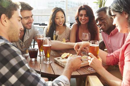 옥상 바에서 음료와 스낵을 즐기는 친구의 그룹 스톡 콘텐츠