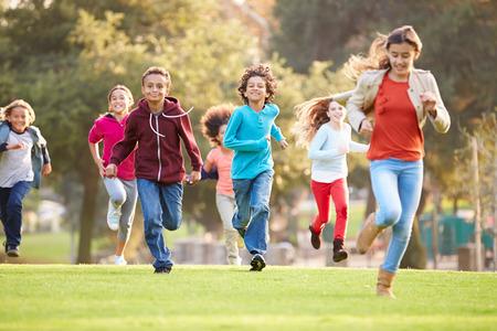 공원에서 카메라를 향해 실행하는 젊은 아이들의 그룹 스톡 콘텐츠