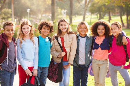 niño con mochila: Grupo de niños jovenes que cuelgan hacia fuera en el parque