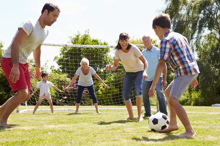Multi Generation Playing Football In Garden Together Imagens