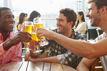 personas celebrando: Tres Amigos masculinos que disfrutan de la bebida en el bar de la azotea al aire libre Foto de archivo