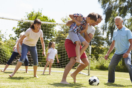women playing soccer: Multi Generation Playing Football In Garden Together Stock Photo