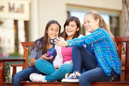 12 13 years: Group Of Girls Taking Selfie On Mobile Phone