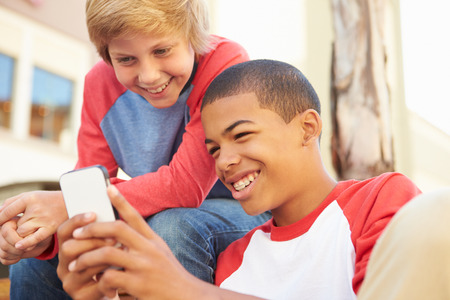 smiling teenagers: Two Teenage Boys Reading Text On Mobile Phone