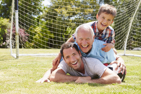 family having fun: Grandfather, Grandson And Father With Football In Garden