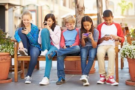 niños sentados: Grupo de niños que se sienta en el centro comercial El uso de teléfonos móviles