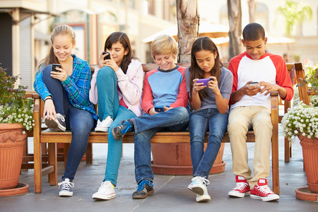 ZELLEN: Gruppe Kinder, die sitzen in der Mall Mit Mobile Phones