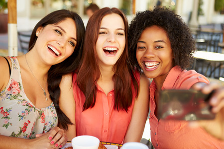 women only: Three Female Friends Taking Selfie In Caf� Stock Photo