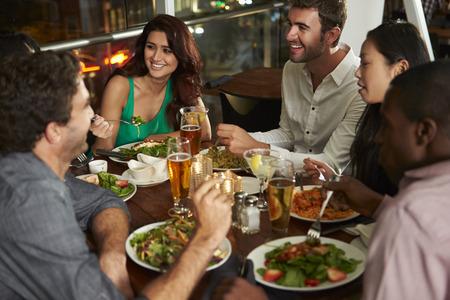 hombre tomando cerveza: Grupo de amigos que disfrutan cena en restaurante Foto de archivo
