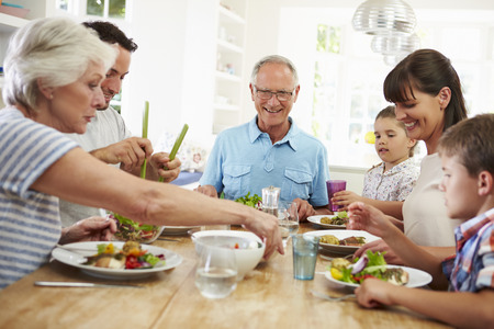 multi generation family: Multi Generation Family Eating Meal Around Kitchen Table Stock Photo