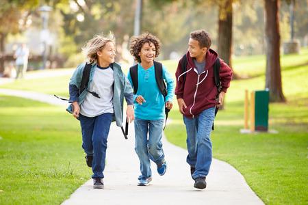 ni�o con mochila: Grupo de j�venes muchachos corriendo hacia la c�mara en el parque