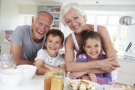 キッチンで朝食を食べて孫を持つ祖父母