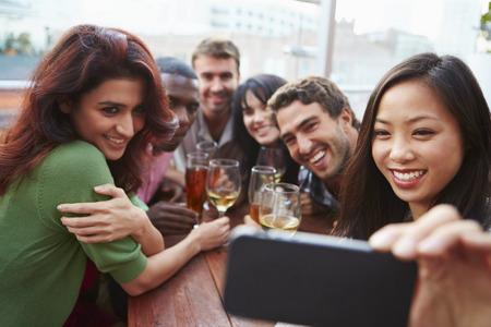 hombre tomando cerveza: Grupo de amigos que toman la fotografía Al aire libre en la azotea Bar Foto de archivo
